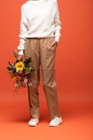 Foto de Vista parcial de la mujer en traje de otoño con la mano en el bolsillo sosteniendo ramo de flores en naranja - Imagen libre de derechos