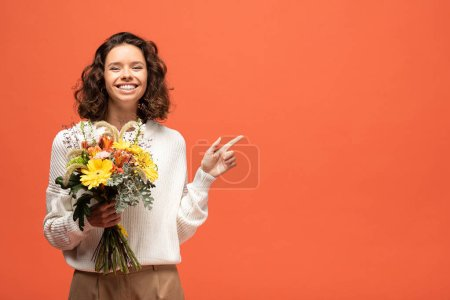 Photo for Happy woman in autumnal outfit holding bouquet of flowers and pointing with finger isolated on orange - Royalty Free Image