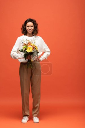 Photo for Happy woman in autumnal outfit holding bouquet of flowers with hand on hip on orange - Royalty Free Image