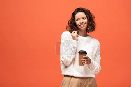 Photo pour Souriant timide femme tenant café pour aller isolé sur orange - image libre de droit