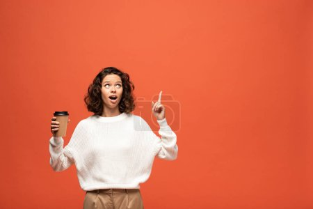 Photo for Excited woman holding coffee to go and showing idea gesture isolated on orange - Royalty Free Image
