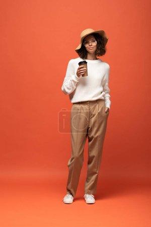 Photo pour Femme dans le chapeau et les glaces retenant le café pour aller sur l'orange - image libre de droit
