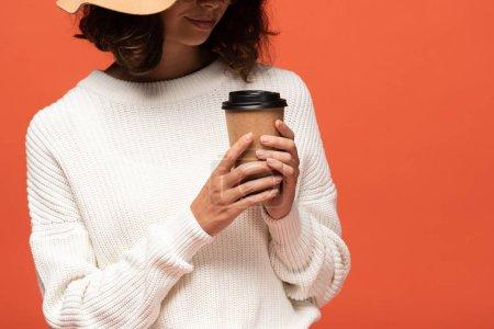 abgeschnittene Ansicht einer Frau mit Hut, die Kaffee zum Isolieren auf Orange hält