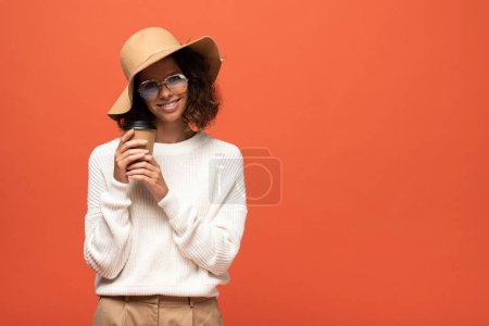 Photo pour Femme souriante dans un chapeau et des lunettes tenant du café pour aller isolé sur orange - image libre de droit