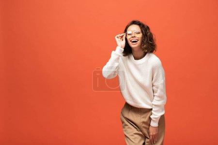 Photo pour Femme heureuse en tenue automnale et lunettes isolées sur orange - image libre de droit