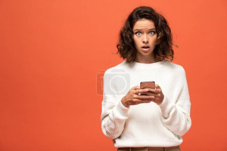 Photo pour Femme choquée en tenue automnale en utilisant smartphone isolé sur orange - image libre de droit