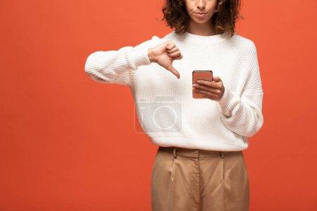 Foto de Vista recortada de la mujer en traje de otoño usando teléfono inteligente y mostrando el pulgar hacia abajo aislado en naranja - Imagen libre de derechos