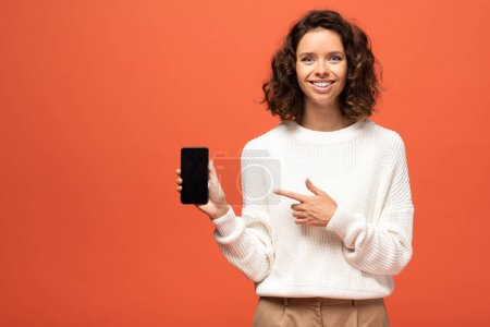 smiling woman in autumnal outfit pointing with finger at smartphone with blank screen isolated on orange