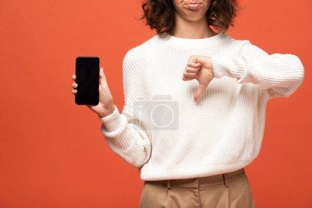 Photo pour Vue recadrée de la femme en tenue automnale tenant smartphone avec écran blanc et montrant pouce vers le bas isolé sur orange - image libre de droit