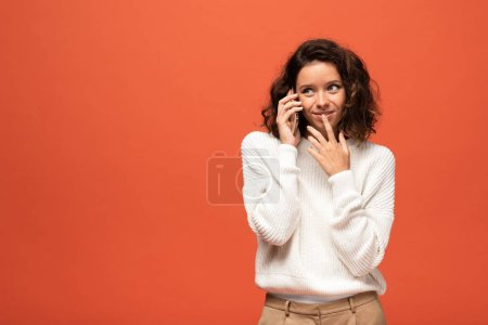 Photo for Smiling curly woman talking on smartphone isolated on orange - Royalty Free Image