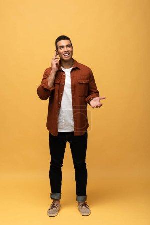 Photo pour Homme mélangé de course de sourire parlant sur le smartphone d'isolement sur le jaune - image libre de droit