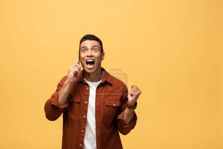 Photo pour Homme heureux de course mélangé parlant sur le smartphone et affichant le geste de oui isolé sur le jaune - image libre de droit