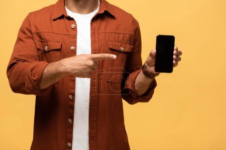 Photo for Cropped view of mixed race man pointing with finger at smartphone with blank screen isolated on yellow - Royalty Free Image