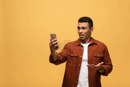 Photo for Displeased mixed race man using smartphone isolated on yellow - Royalty Free Image