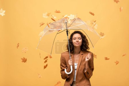 happy curly woman in brown jacket with closed eyes holding umbrella in falling golden maple leaves isolated on yellow