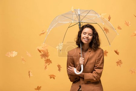 happy curly woman in brown jacket holding umbrella in falling golden maple leaves isolated on yellow