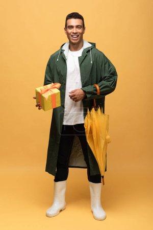 Foto de Hombre de carrera mixto en impermeable y botas de goma sosteniendo caja de regalo y paraguas aislado en amarillo - Imagen libre de derechos