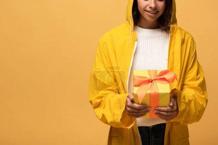 Photo pour Vue recadrée de la femme souriante en imperméable jaune tenant boîte cadeau isolé sur jaune - image libre de droit