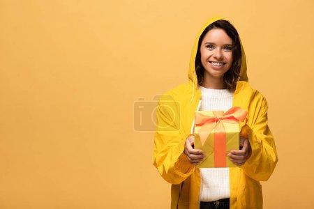 Photo pour Heureuse femme bouclée en imperméable jaune tenant boîte cadeau isolé sur jaune - image libre de droit