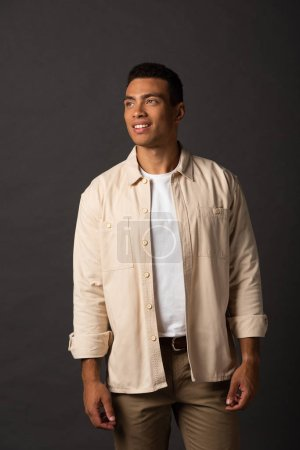 Photo for Smiling handsome mixed race man in beige shirt looking away on black background - Royalty Free Image