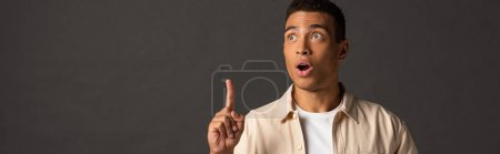 Photo for Panoramic shot of handsome mixed race man in beige shirt showing idea gesture on black background - Royalty Free Image