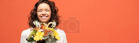 Photo for Panoramic shot of happy woman in autumnal outfit holding bouquet of flowers isolated on orange - Royalty Free Image