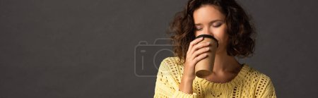 Photo for Panoramic shot of curly woman in yellow knitted sweater with closed eyes holding coffee to go on black background - Royalty Free Image