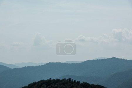 Photo pour Nuages blancs sur le ciel près des montagnes avec des arbres verts - image libre de droit