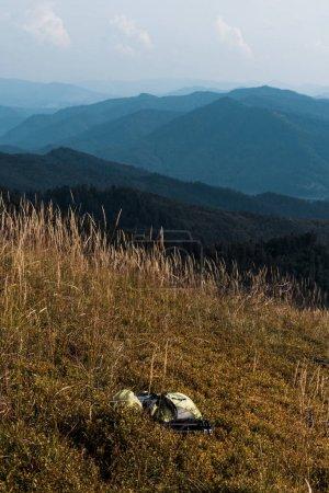 Photo pour Pré jaune avec l'orge près du sac à dos dans les montagnes contre le ciel - image libre de droit