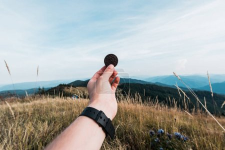 Photo for CARPATHIANS, UKRAINE - AUGUST 24, 2019: cropped view of man holding oreo cookie in field near mountains - Royalty Free Image
