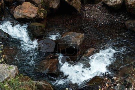 Photo pour Vue aérienne des roches près du ruisseau coulant dans la forêt - image libre de droit