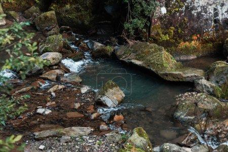 Photo pour Mise au point sélective de l'eau qui coule près des pierres humides - image libre de droit
