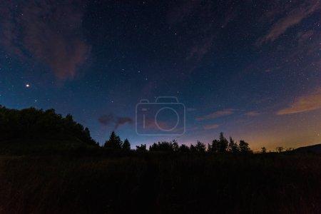 Photo pour Ciel bleu avec des étoiles brillantes et des nuages la nuit - image libre de droit