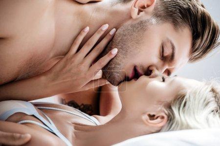 Photo pour Attrayant femme en blanc sous-vêtements baisers avec bel homme dans l'appartement - image libre de droit
