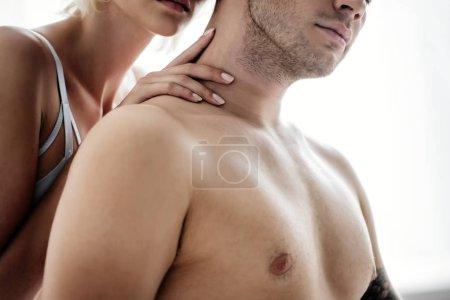 recortado vista de la mujer abrazando sin camisa hombre en apartamento