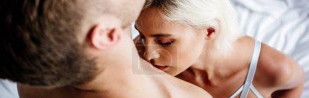Photo pour Panoramic shot of blonde salope and attractive woman kissing man - image libre de droit