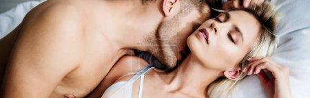 Photo pour Photo panoramique d'un homme embrassant une belle femme aux yeux fermés - image libre de droit