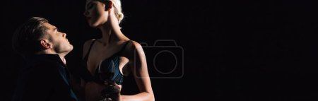 Photo pour Panoramic shot of woman in black underwear holding wine glass and hugging man - image libre de droit