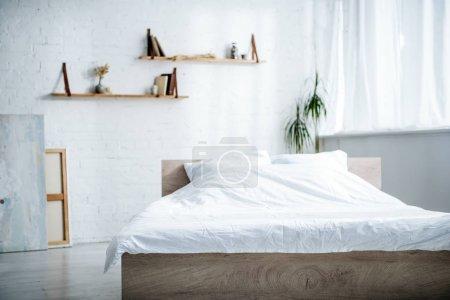 Schlafraum mit Bett, Kissen, Decke, Regalen und Pflanzen