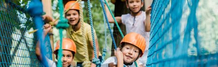Photo for Panoramic shot of happy multicultural climbers in helmets - Royalty Free Image