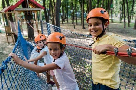 Photo pour Des enfants heureux se tenant debout sur une corde haute - image libre de droit