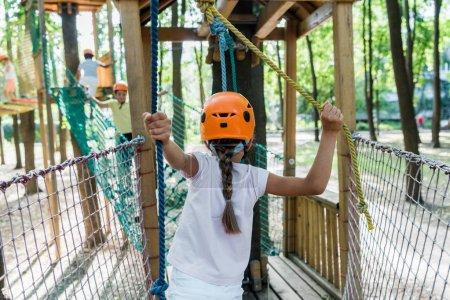 Photo pour Retour vue d'un enfant portant un casque dans un parc d'aventure - image libre de droit