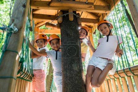 Photo pour Des enfants joyeux et multiculturels portant des casques souriants tout en regardant la caméra - image libre de droit