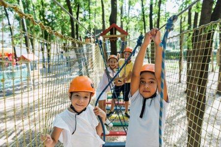 Photo pour Focalisation sélective des enfants positifs et multiethniques dans le parc d'aventure - image libre de droit