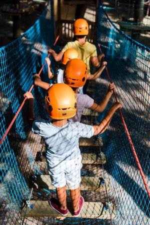 Photo pour Retour vue de quatre enfants multiculturels portant un casque dans un parc d'aventure - image libre de droit