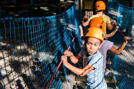 Photo pour Foyer sélectif du garçon afro-américain sur la piste de corde haute avec des amis - image libre de droit