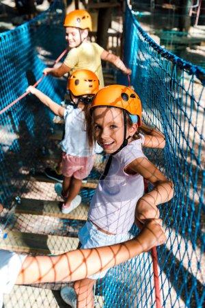 Photo pour Le point de mire sélectif d'un enfant joyeux et mignon sur un sentier de haute corde avec des amis - image libre de droit