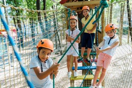 Photo pour Centre d'intérêt sélectif des enfants multiculturels dans le parc d'aventure sur la corde haute - image libre de droit