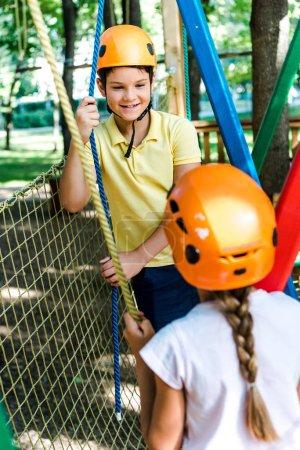 Photo pour L'attention sélective d'un garçon regardant un enfant dans un casque extérieur - image libre de droit