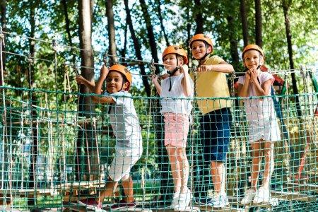 Photo pour Happy multicultural boys near friends in helmets in adventure park - image libre de droit